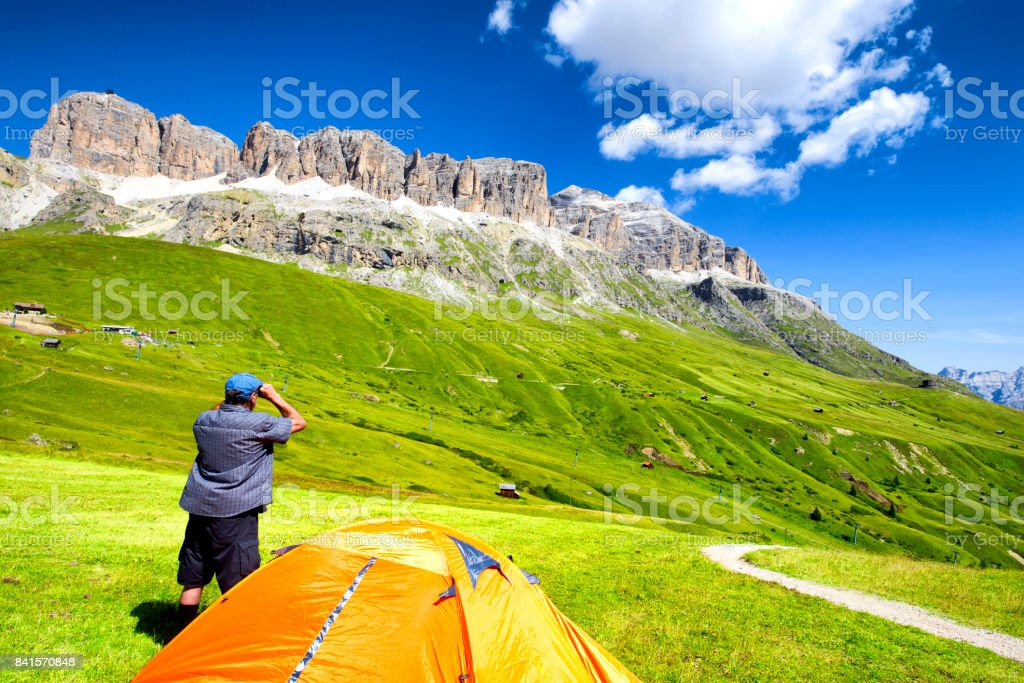 Man with binoculars in Dolomites Alps stock photo