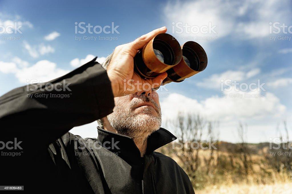 Man with  binoculars Man with binoculars in a field Binoculars Stock Photo