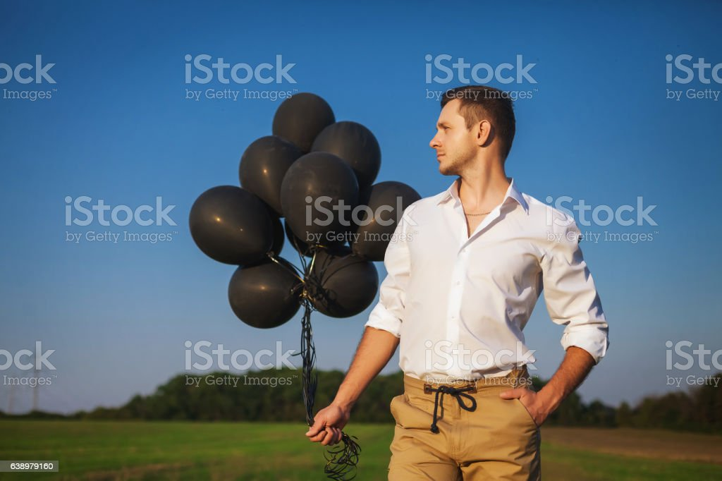 man with black balloons standing in field and looks into stock photo