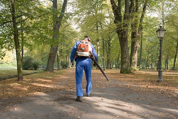 mann mit blauer strampler reinigung gehweg im park (xxl - jumpsuit blau stock-fotos und bilder