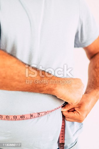 istock Man with blue t-shirt taking measures size of the belly - fat and diet concept for people try to stay healthy and build a better body - 1130886117