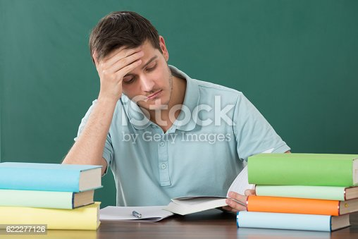 840623324istockphoto Man With Books At Desk 622277126