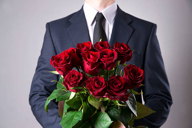 Man with bouquet of red roses on a gray background stock photo