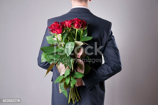 istock Man with bouquet of red roses on a gray background 522532276