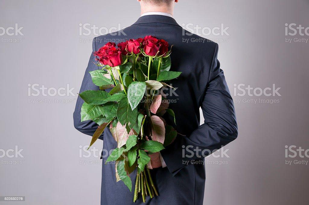 Человек с Букет из красных роз на серый фон стоковое фото