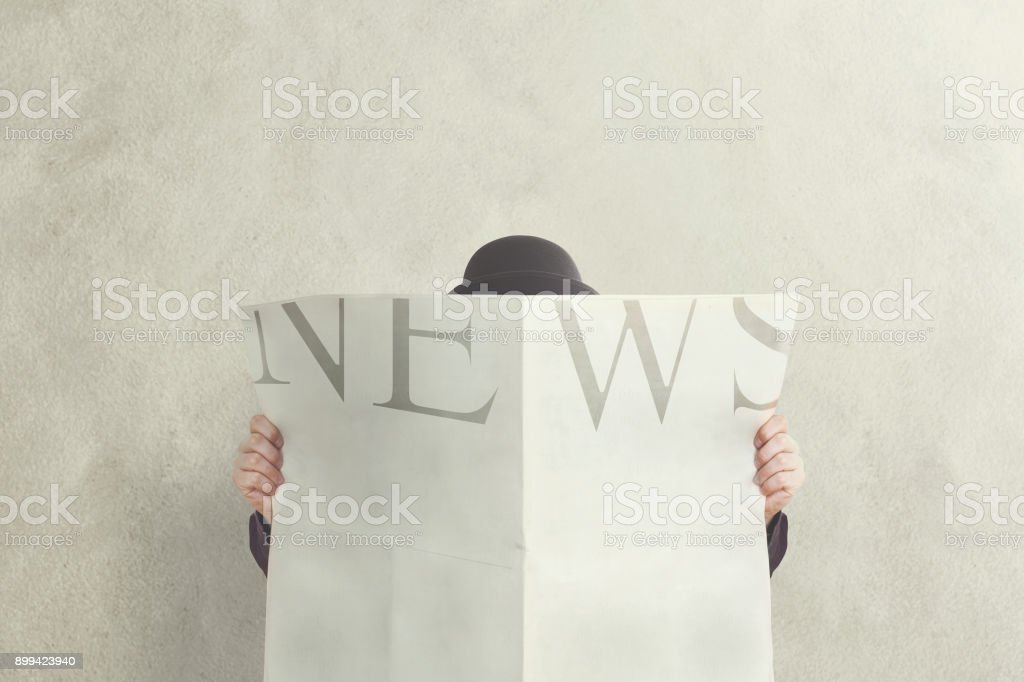man with bowler holding reading news stock photo