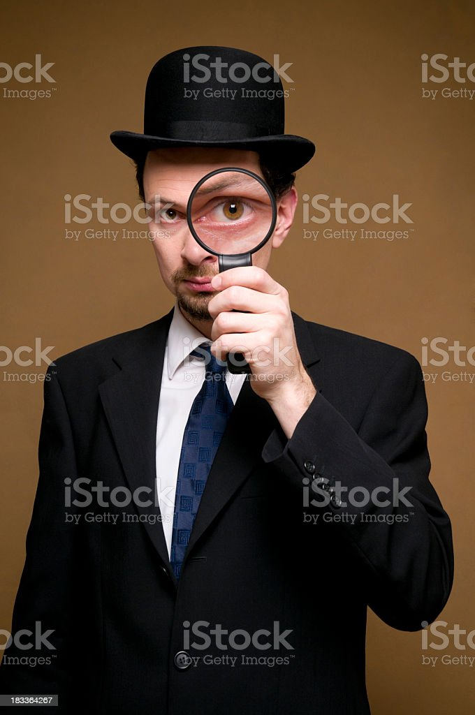 man with bowler looking through a magnifier stock photo