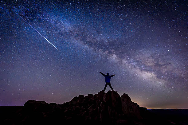 man with bright shooting star under milky way galaxy - shooting stars stock photos and pictures
