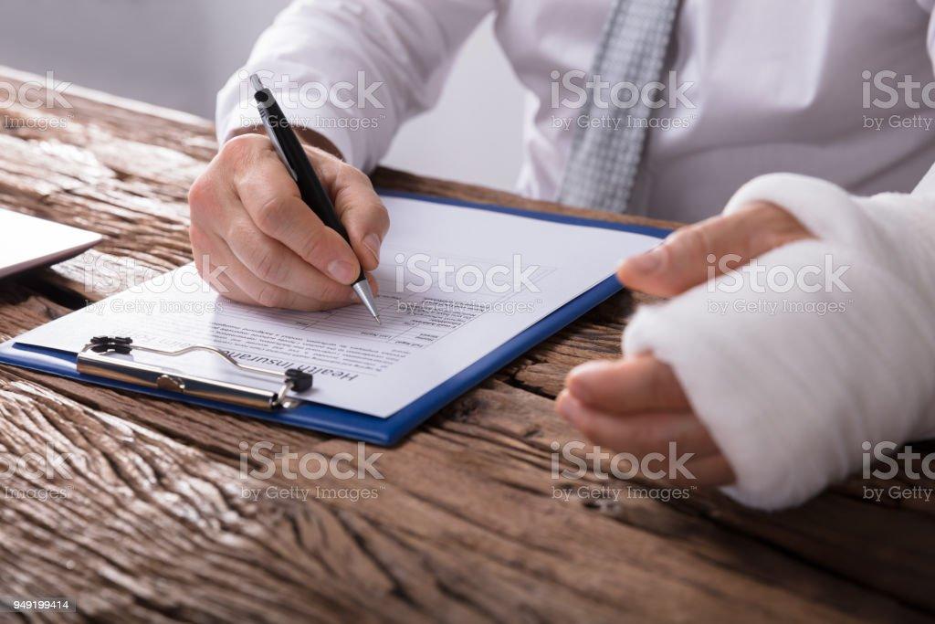 Hombre con el brazo roto, llenando el formulario de reclamación de seguro de salud - foto de stock