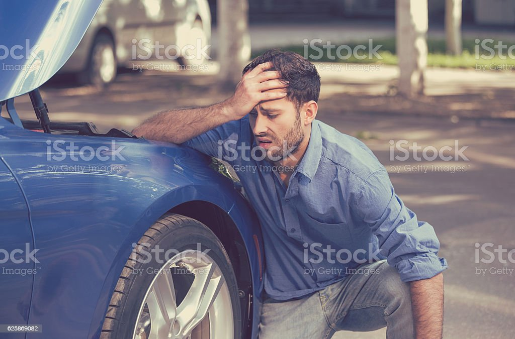 Man with broken down car flat tire stock photo