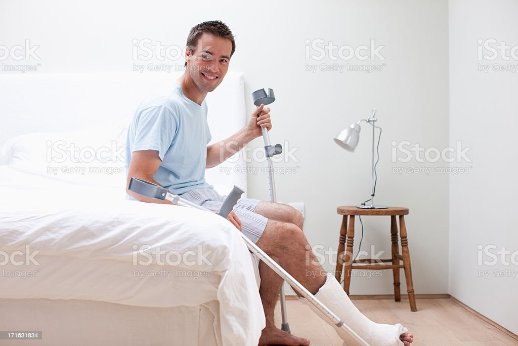 Man with broken leg sitting on bed stock photo