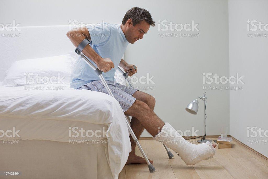 Człowiek Z Złamana Noga Próbuje Wstać Z łóżka Zdjęcia