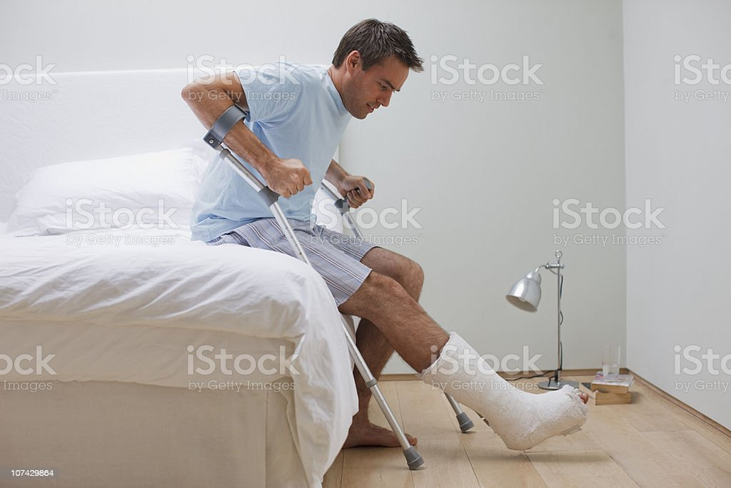 Man with broken leg trying to get up from bed stock photo