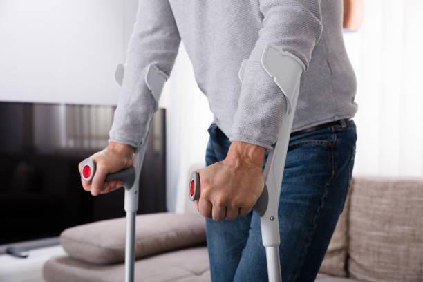 松葉杖を使用して壊れた脚を持つ男 - 杖 ストックフォトと画像