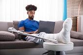 Man With Broken Leg Using Laptop