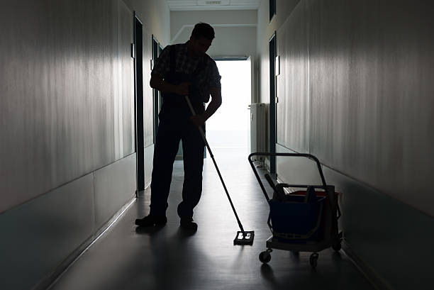 man with broom cleaning office corridor - custodian stock pictures, royalty-free photos & images