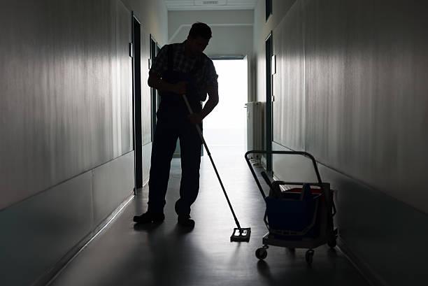 mann mit besen reinigung büro-korridor - hausmeister stock-fotos und bilder