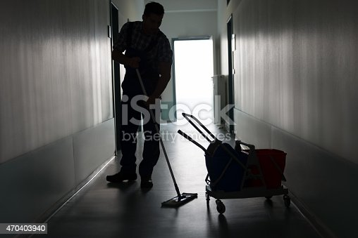 istock Man With Broom Cleaning Office Corridor 470403940