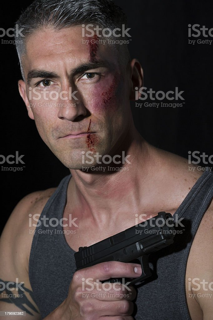 Man with bruises and cut lip holding a handgun stock photo