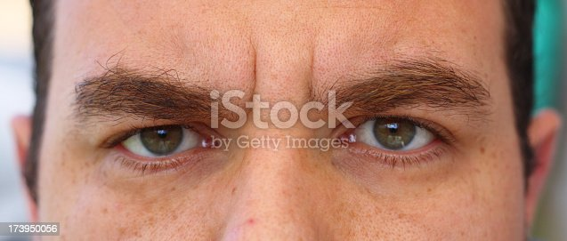 A close-up of a man showing only his eyes and his bushy eyebrows.