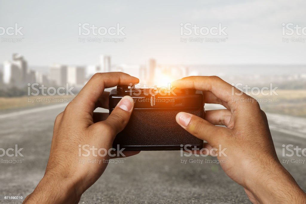 Man with camera in hands . Mixed media stock photo