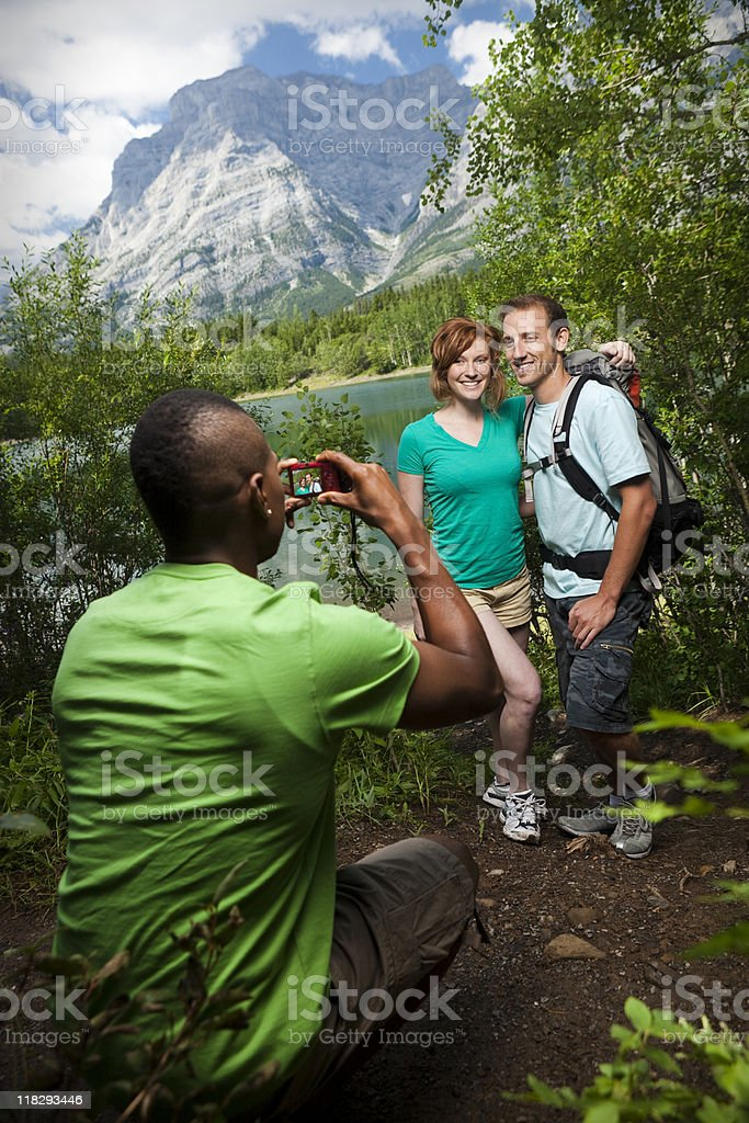 Man with Camera taking Photo of Couple in Mountain royalty-free stock photo