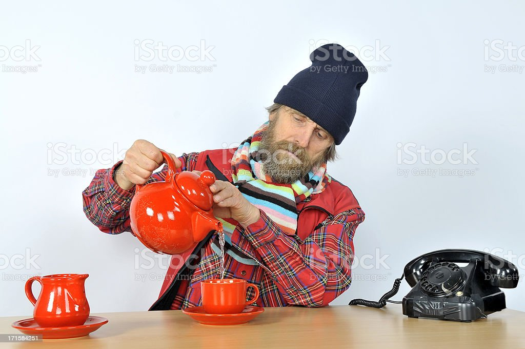 Man with Cap and Scarf Pouring his Tea royalty-free stock photo