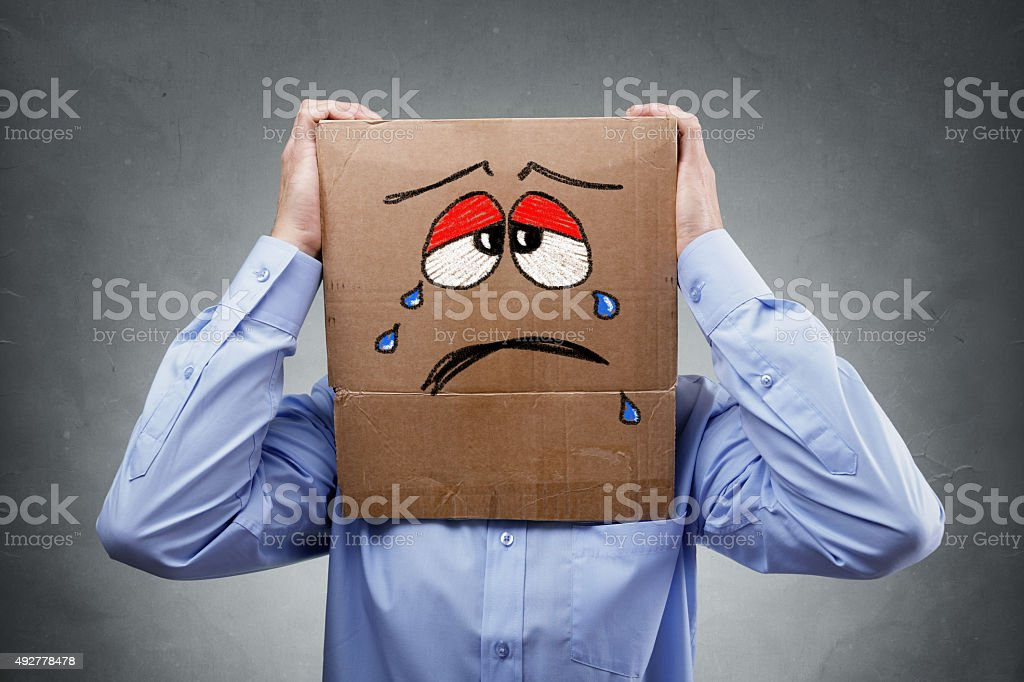 Man with cardboard box on his head showing sad expression stock photo