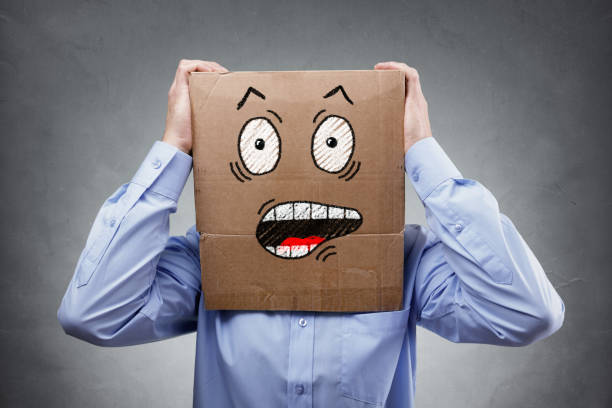 Man with cardboard box on his head showing shocked and surprised expression stock photo