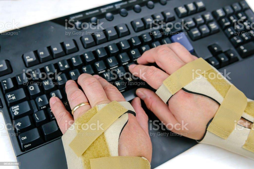 Mann mit Karpal-Tunnel-Syndrom, rheumatoide Arthritis oder Arthrose und tragen Handgelenksschienen mit einer Computertastatur – Foto