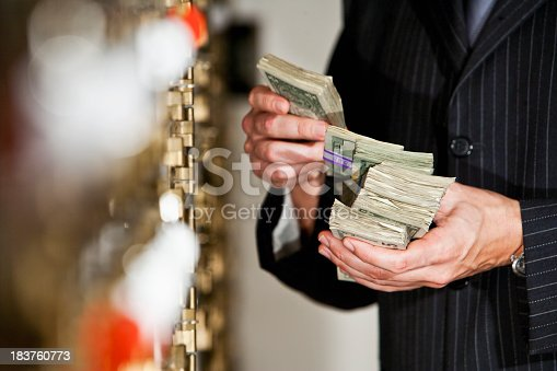 Man holding big stack of US paper currency by safety deposit boxes.  Focus on money