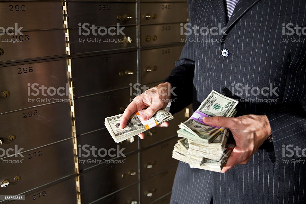 Man with cash by safety deposit boxes stock photo