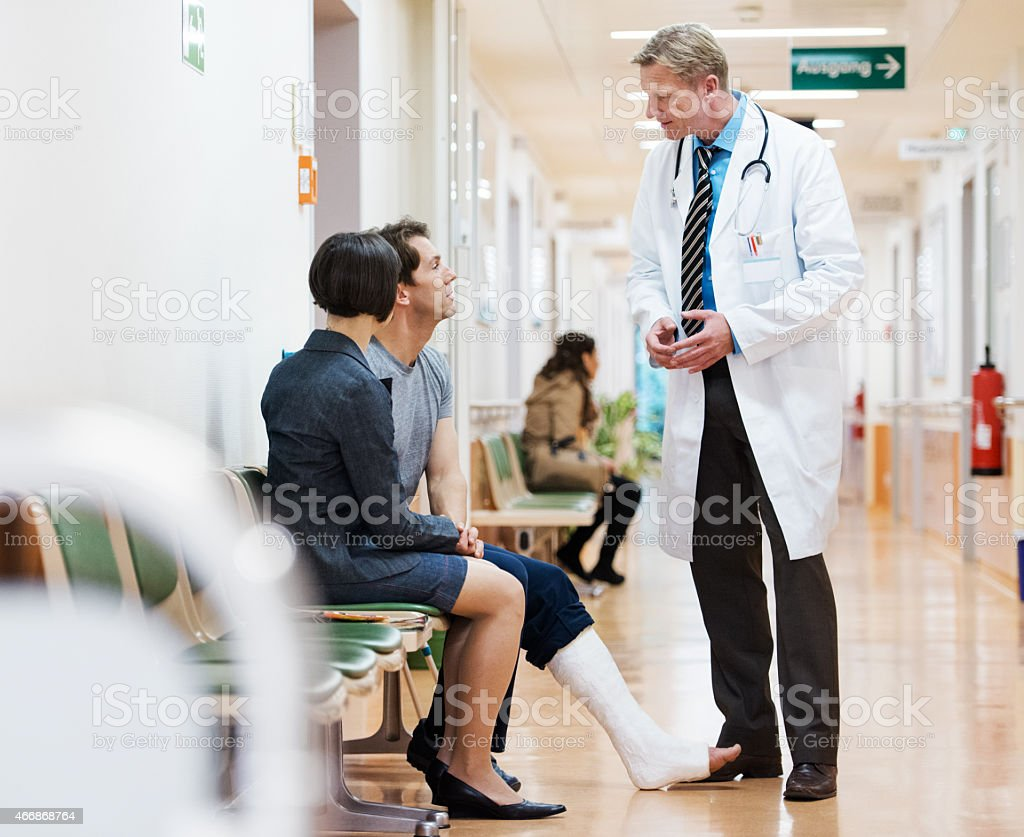 Man With Cast On Broken Leg Consulting Doctor stock photo