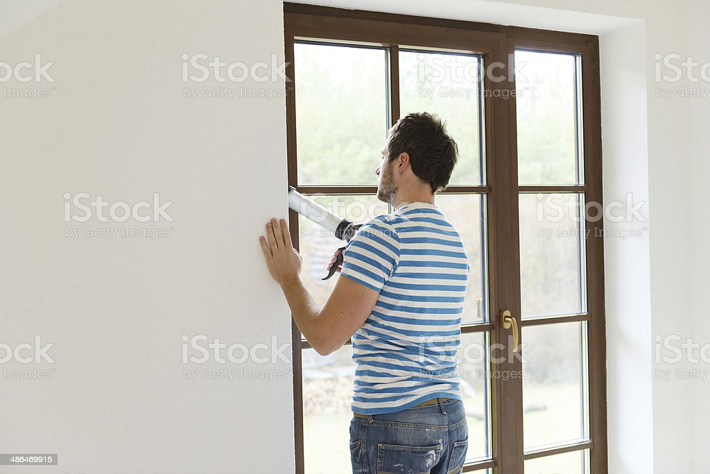 Man with caulking gun stock photo