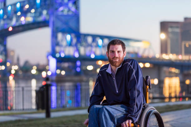 Man with cerebral palsy in wheelchair at city waterfront stock photo