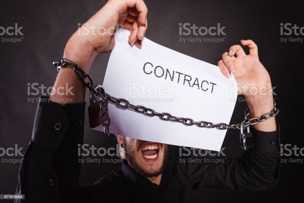 Man with chained hands holding contract royalty-free stock photo