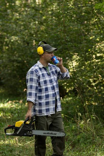 man with chainsaw in the forest is drinking pepsi cola stock photo