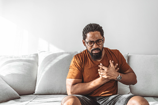 Man with chest pain suffering from heart attack while sitting at home during the day.