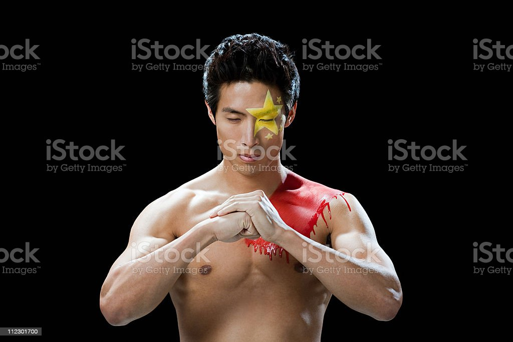 Man with Chinese flag painted on face and shoulder, making fist royalty-free stock photo