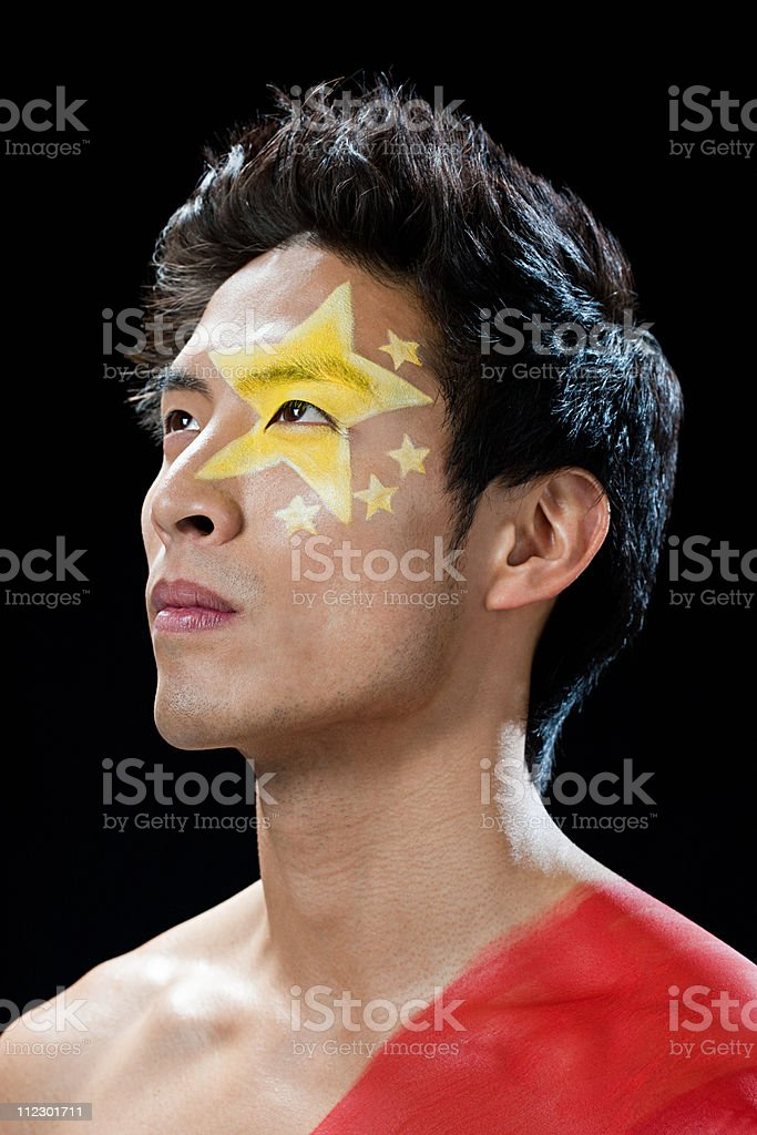 Man with Chinese flag painted on face and shoulder royalty-free stock photo