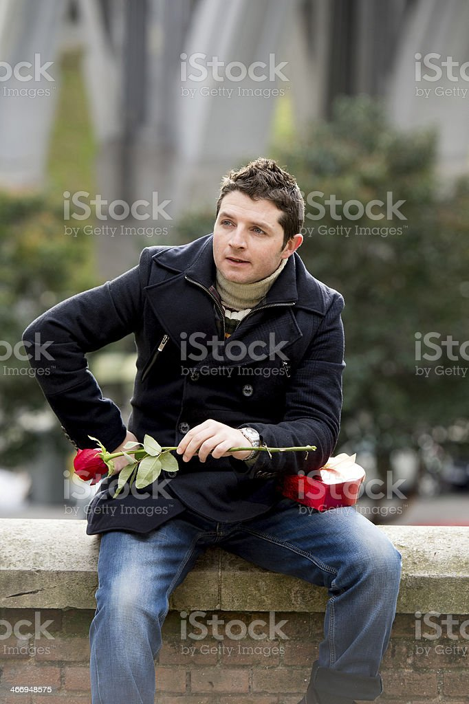 man with chocolates and a rose being stood up stock photo