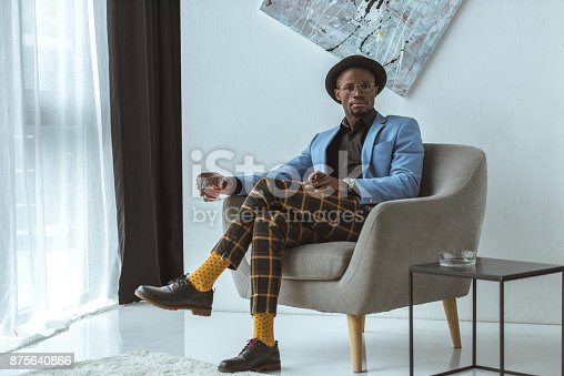 stylish african american man in hat, checkered pants and blue jacket with cigar and glass of cognac sitting in armchair in modern office