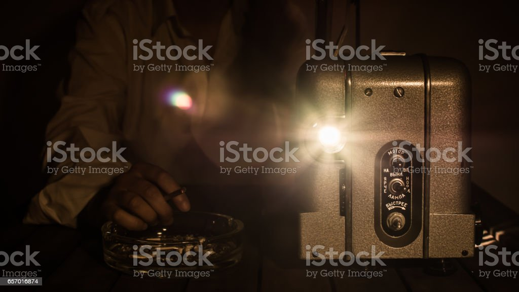 Man with cigarette watching movie on old projector. stock photo