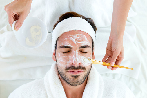 istock Man with clay facial mask in beauty spa. 514032693