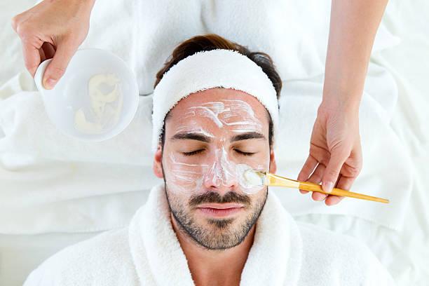Homme dans un masque à l'argile du visage au spa beauté. - Photo
