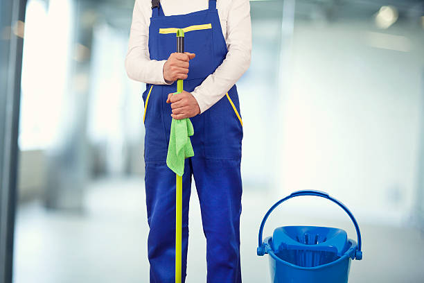 Man with cleaning supplies in building stock photo