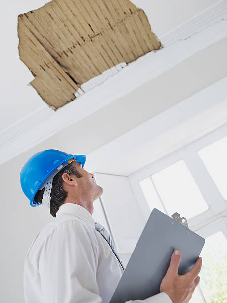Man with clipboard and helmet looking at ceiling in house stock photo