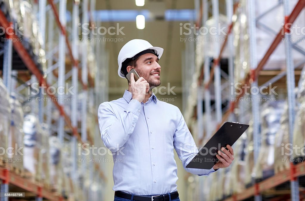 man with clipboard and smartphone at warehouse stock photo