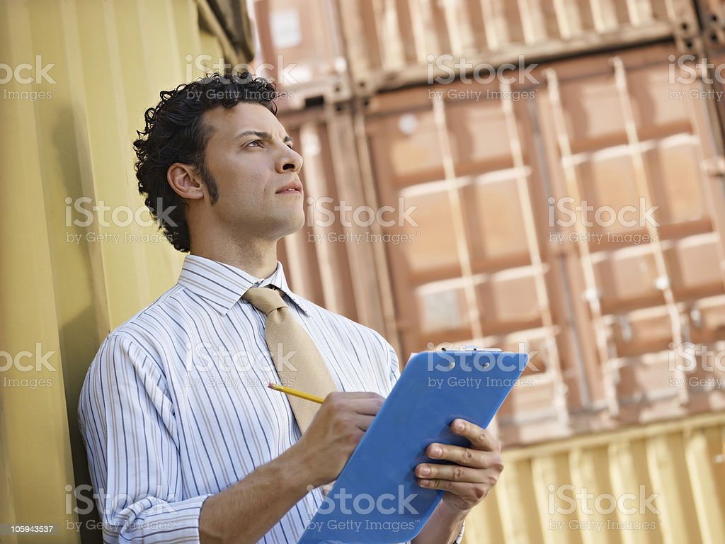 Man with clipboard looking at containers royalty-free stock photo