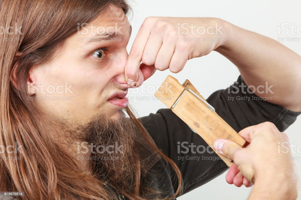 Man with clogged nose by clothespin stock photo